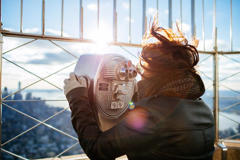 Frau mit Feldstecher schaut über die Stadt | bewusstgluecklich.ch